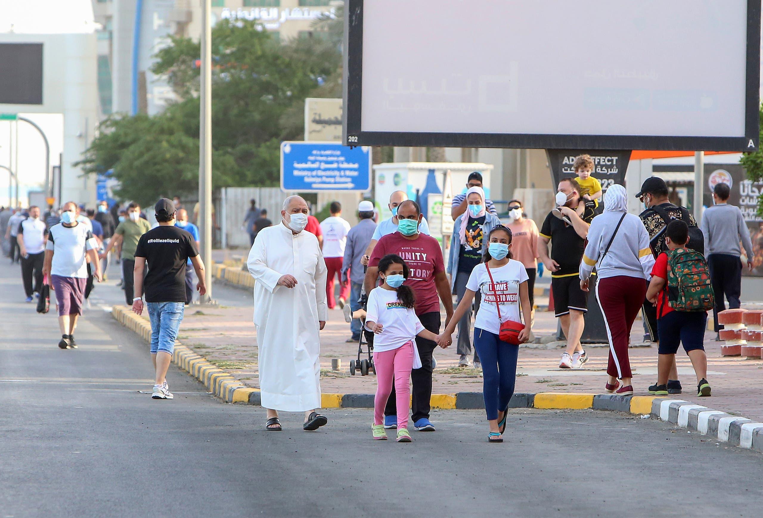 سكان العاصمة الكويتية يتنزهون مرتدين الكمامات