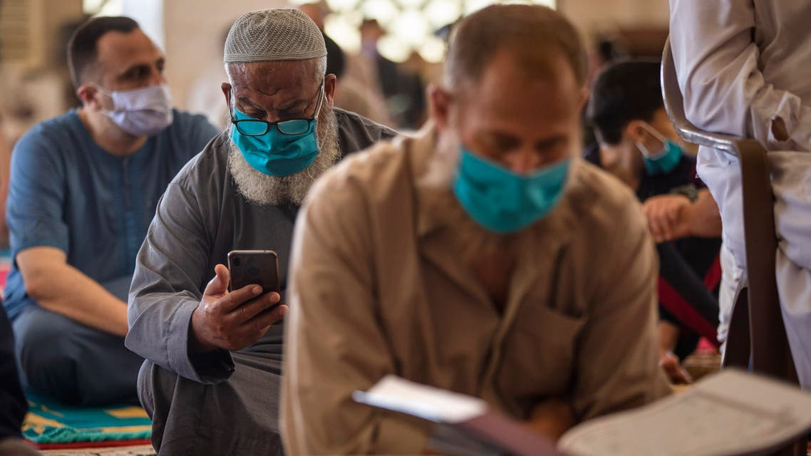 Palestinians wearing face masks read the Quran as they attend the last Friday noon Prayer of the holy month of Ramadan, in a mosque in Gaza City, Friday, May. 22, 2020. After nearly two months of closure due to the coronavirus, Gaza's Hamas rulers decided to partially reopen mosques for the Friday noon prayer. (AP Photo/Khalil Hamra)