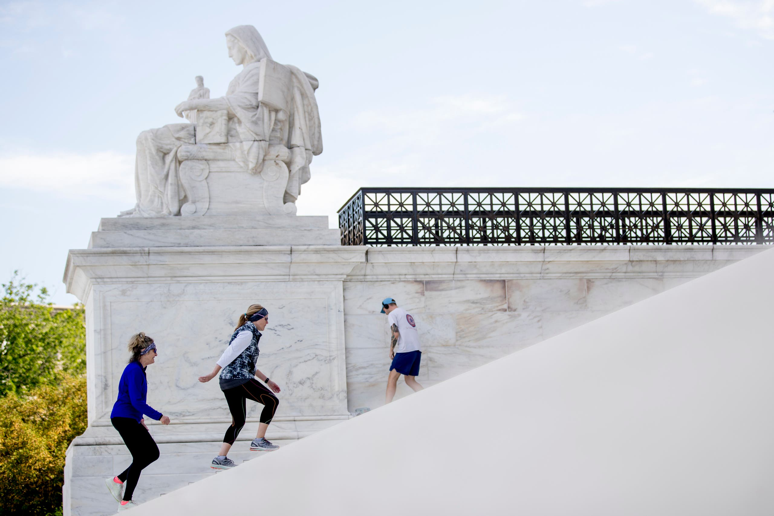 Women exercise on the steps of the US Supreme Court on May 4, 2020, in Washington. (AP)
