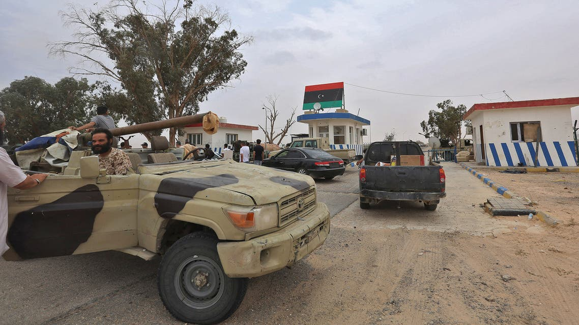 Vehicles of forces loyal to Libya's UN-recognised Government of National Accord (GNA) are seen outside a checkpoint at Al-Watiya airbase also known as Okba Ibn Nafa airbase, which they seized control of, southwest of the capital Tripoli, on May 18, 2020. Libya's UN-recognised government scored another battlefield victory Monday against strongman Khalifa Haftar, capturing the key rear base used by his fighters in a conflict now in its second year. Haftar, who controls swathes of eastern Libya, launched an offensive in April last year against the capital Tripoli, seat of the UN-recognised Government of National Accord (GNA).