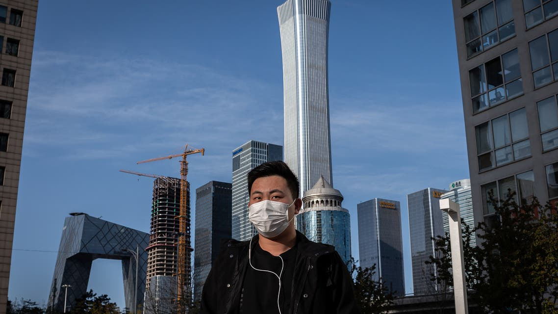 A man wearing a face mask amid the COVID-19 coronavirus outbreak walks outside office buildings in Beijing on April 1, 2020. (AFP)