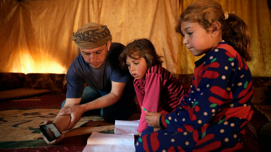In this April 13, 2020 photo, Tariq al-Obeid, displaced from the eastern countryside of Idlib, Syria, shows a lesson for his children on a mobile phone in Kelly, a town in northern Idlib. (AP)