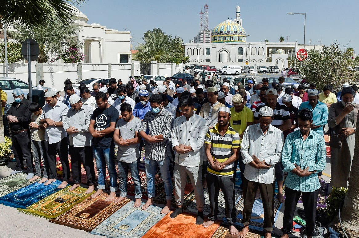 Muslim worshippers, some wearing protective masks, perform together Friday prayers outside a mosque in Bahrain's capital Manama on February 28, 2020. (AFP)