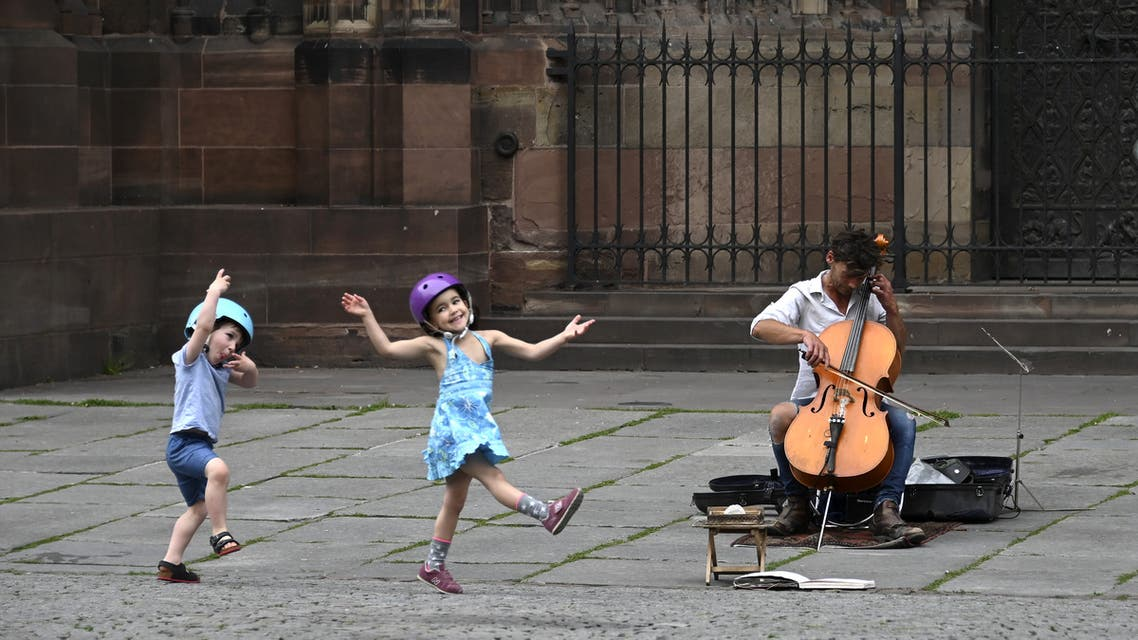 Two children dance as they listen to a street musician on May 22, 2020 in Strasbourg, eastern France. (AFP)
