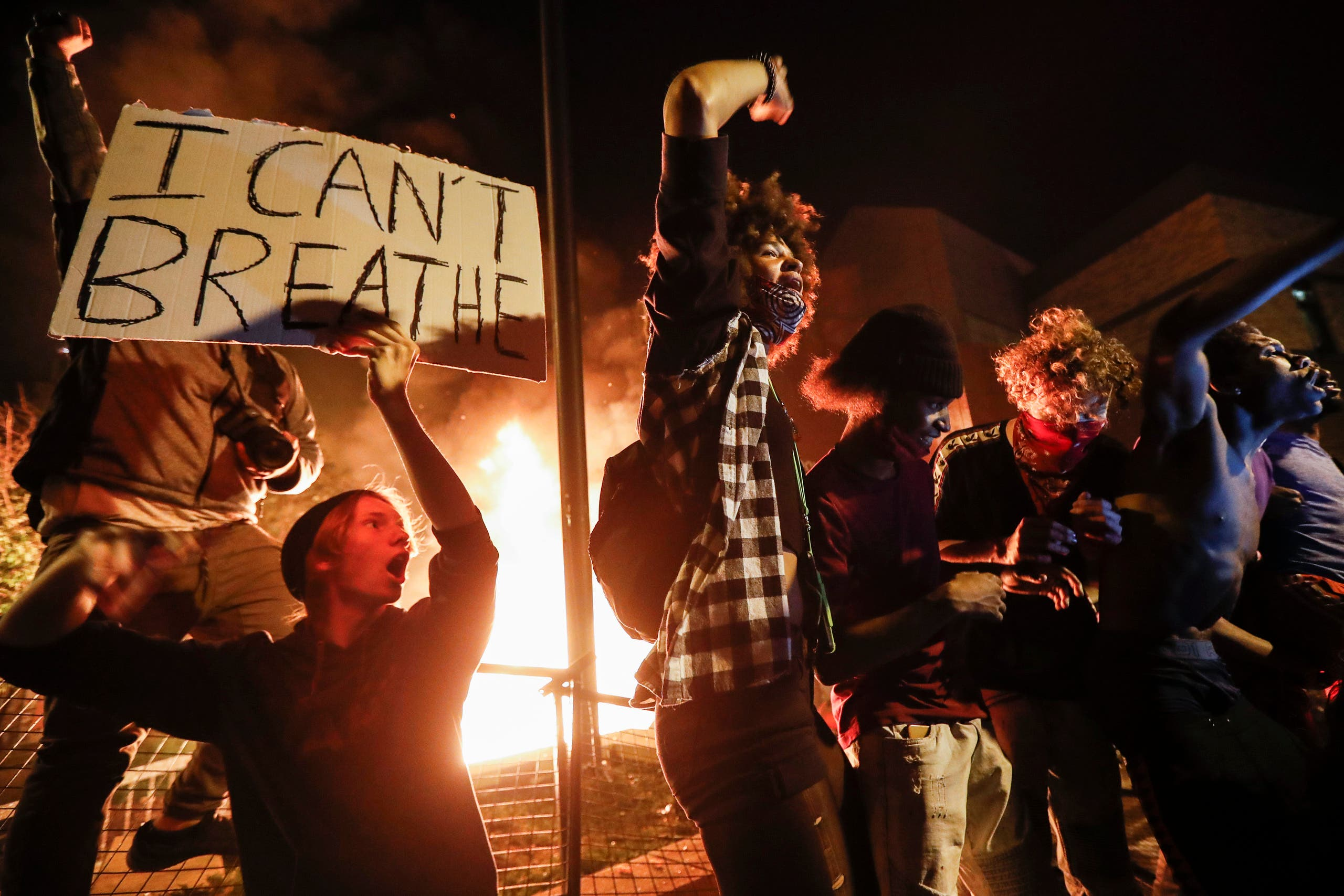 Protestors demonstrate outside of a burning Minneapolis 3rd Police Precinct, Thursday, May 28, 2020, in Minneapolis. Protests over the death of George Floyd, a black man who died in police custody Monday, broke out in Minneapolis for a third straight night. (AP)