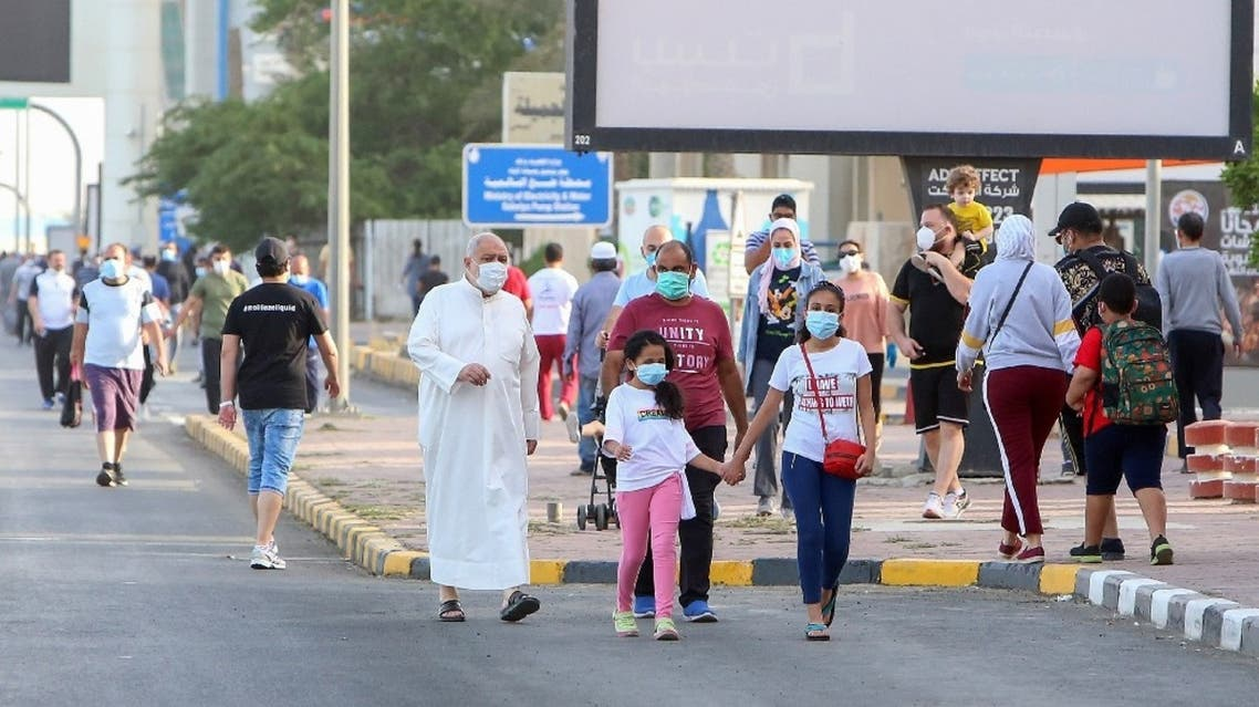 Mask-clad residents walk in a neighbourhood of Kuwait City on May 12, 2020. (AFP)