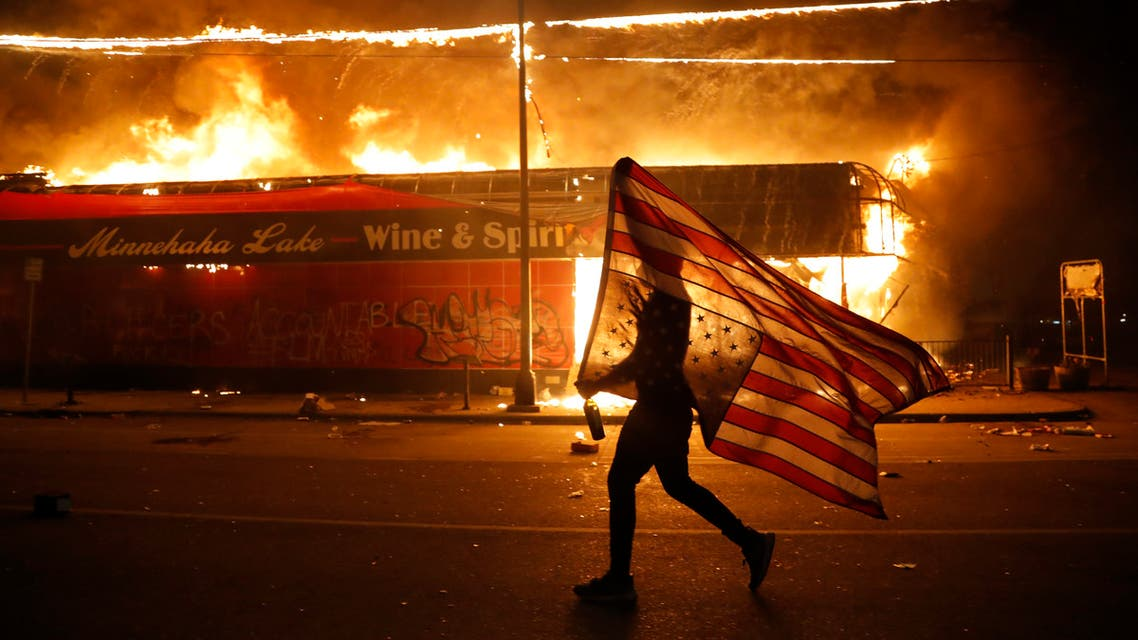 A protester carries a U.S. flag upside down, a sign of distress, next to a burning building Thursday, May 28, 2020, in Minneapolis. Protests over the death of George Floyd, a black man who died in police custody Monday, broke out in Minneapolis for a third straight night. (AP)