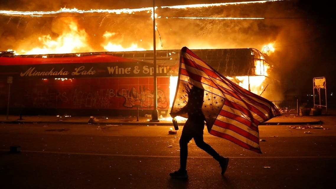 A protester carries the carries a U.S. flag upside, a sign of distress, next to a burning building Thursday, May 28, 2020, in Minneapolis. (AP)