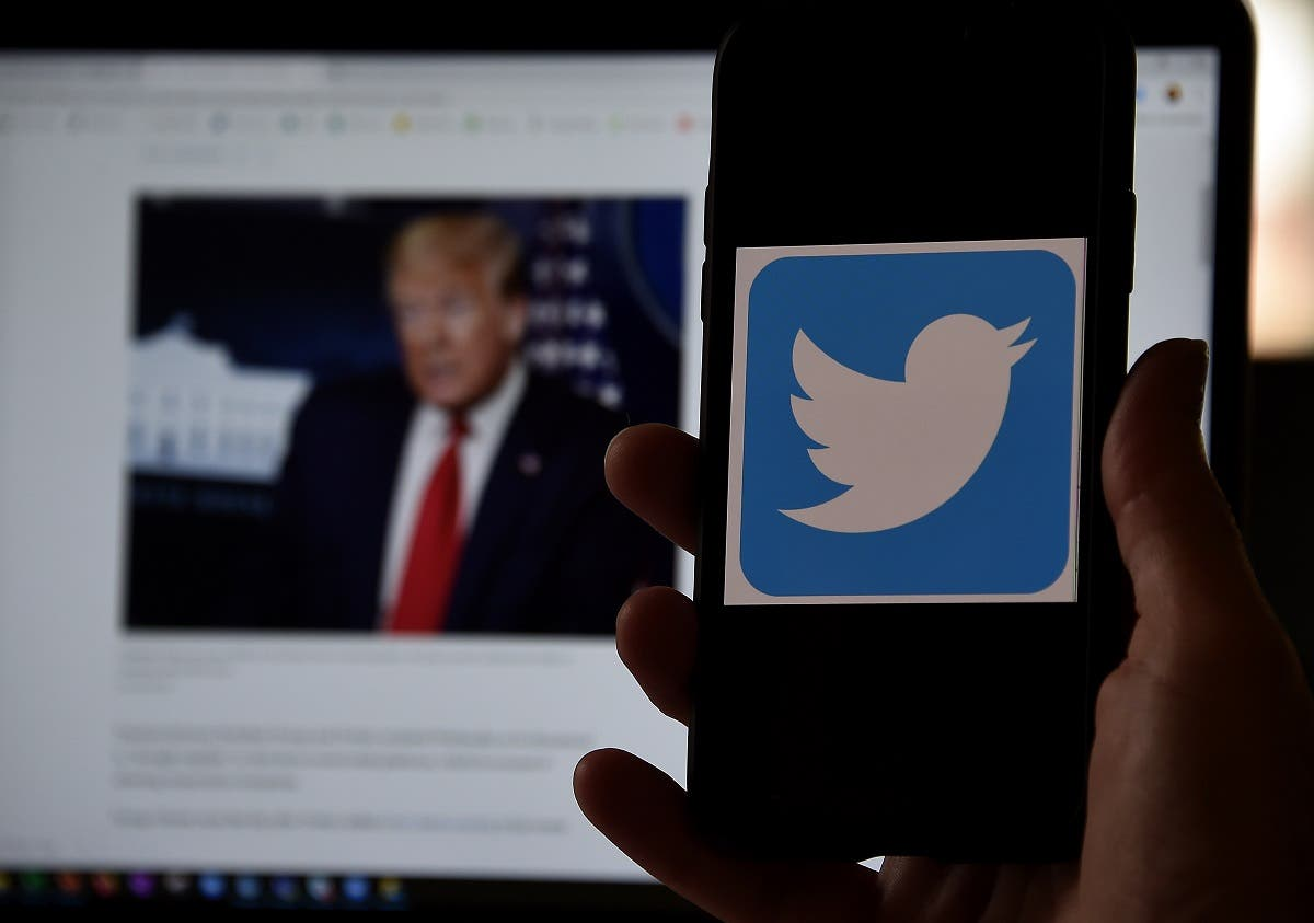 In this photo illustration, a Twitter logo is displayed on a mobile phone with President Trump's Twitter page shown in the background on May 27, 2020, in Arlington, Virginia. (File photo: AFP)