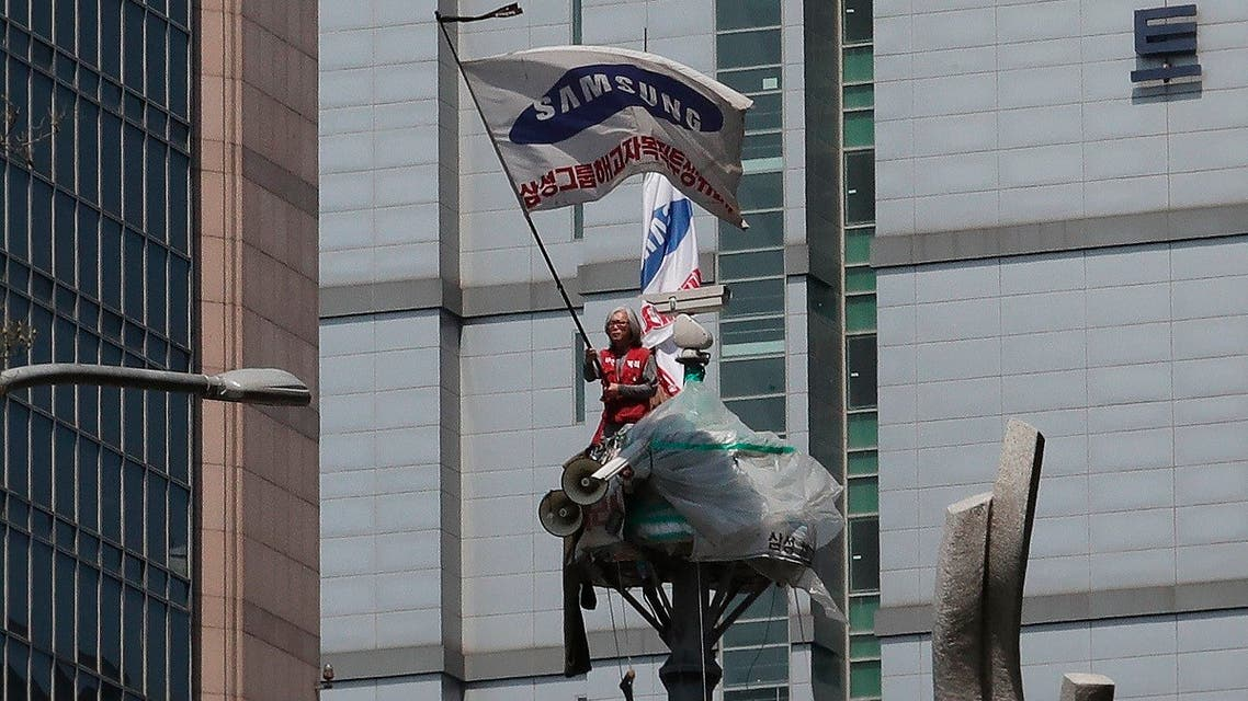 A protester Kim Yong-hee waves a Samsung Group flag against the group's union policy at the top of a traffic camera tower in Seoul, South Korea, Wednesday, May 6, 2020. (AP)