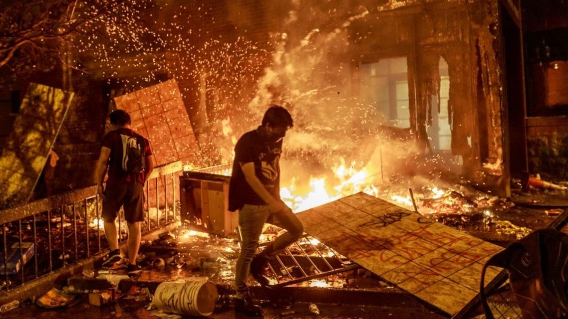Protesters walk past burning debris outside the Third Police Precinct on May 28, 2020 in Minneapolis, Minnesota, US, during a protest over the death of George Floyd. (AFP)