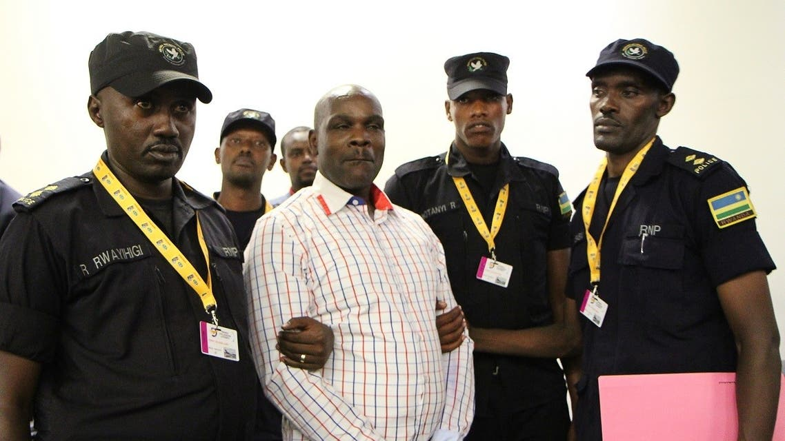Ladislas Ntaganzwa (C) is escorted by police officers upon his arrival at the airport of Kigali, on March 20, 2016. (File photo: AFP)