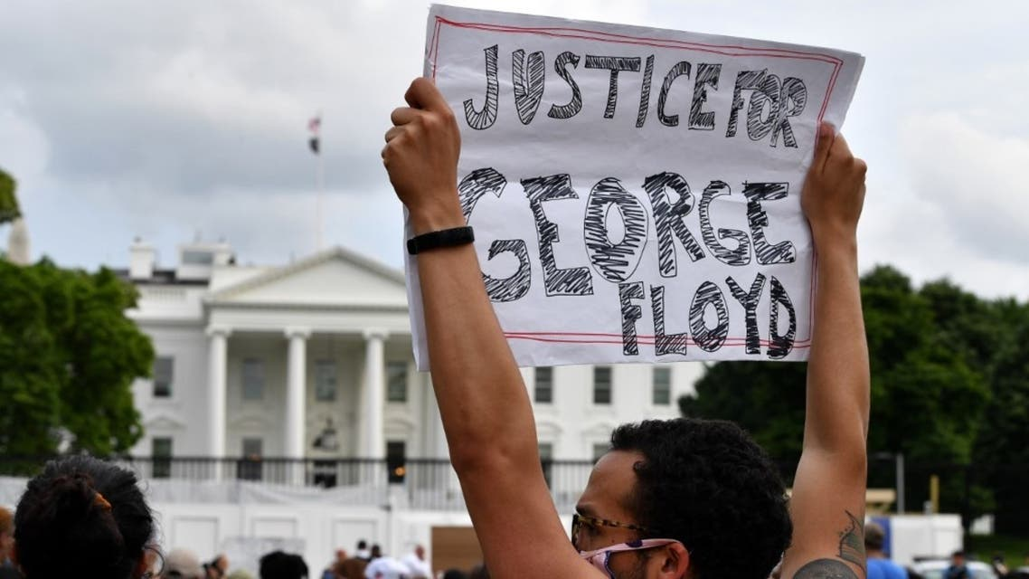 Protesters hold signs as they gather outside the White House in Washington, DC, on May 29, 2020 in a demonstration over the death of George Floyd. (AFP)