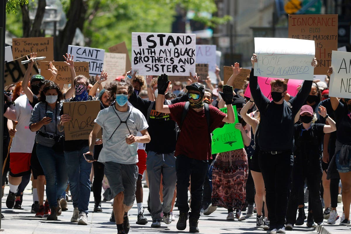 Participants walk with their hands in the air down the 16th Street Mall during a protest over the death of George Floyd, Friday, May 29, 2020, in Denver. More than 1,000 protesters walked from the Capitol down the 16th Street pedestrian mall during the protest. (AP)