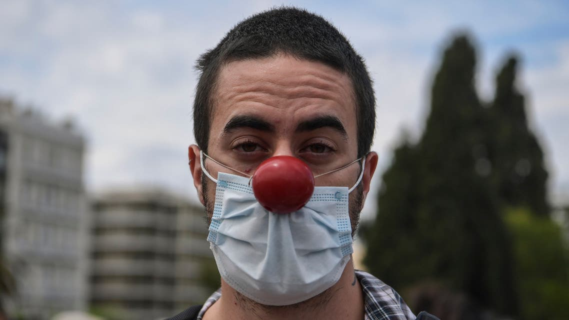 A Greek artist protests wearing a face mask and a red nose in Athens on May 7, 2020. (AFP)