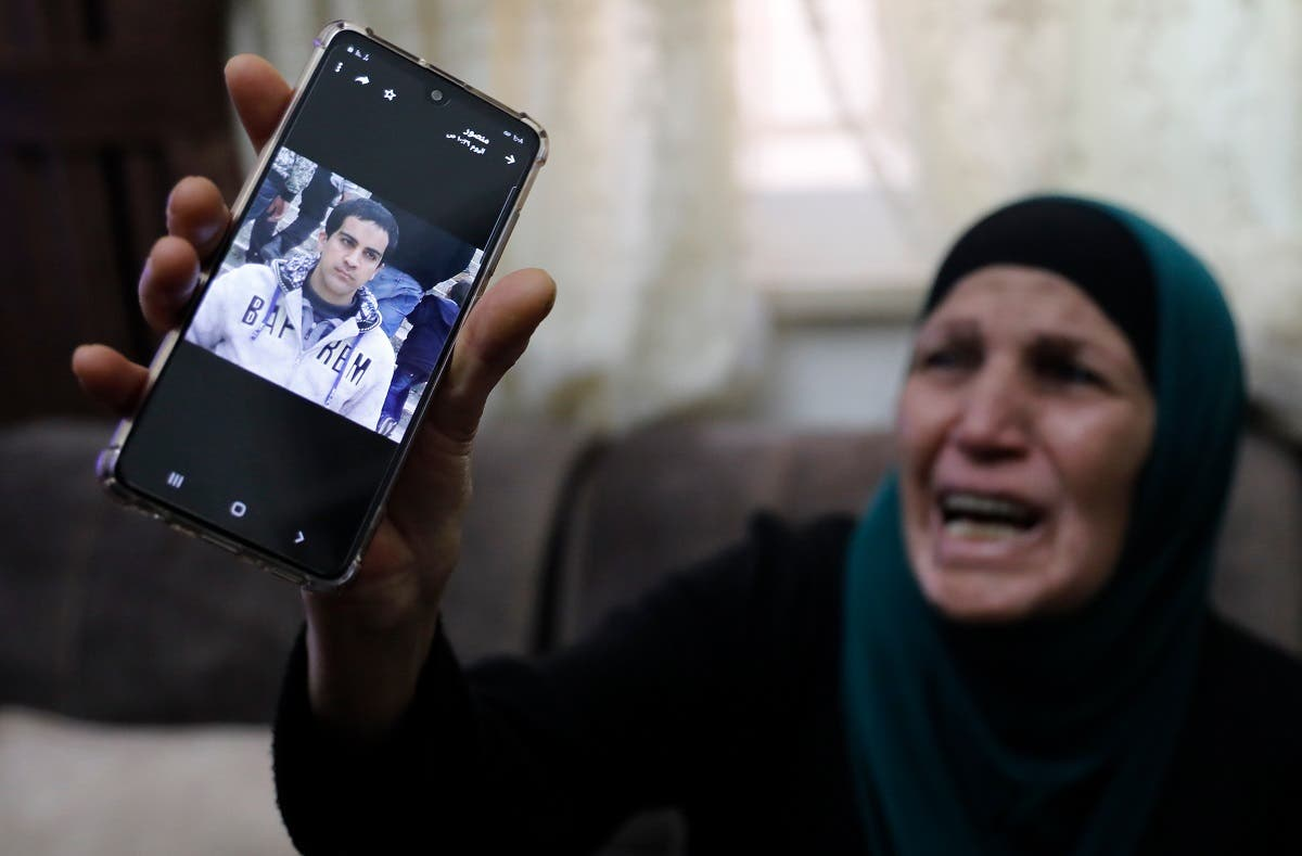 The mother of Iyad Khayri, a Palestinian with special needs, who was shot dead by Israeli police, cries as she shows his picture on her cellphone, at her home in annexed east Jerusalem, on May 30, 2020. (AFP)