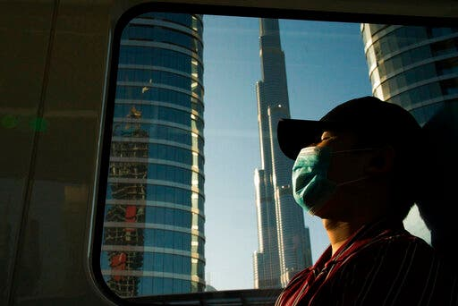 A commuter wearing a face mask as the metro passes the Burj Khalifa in Dubai. (AP)