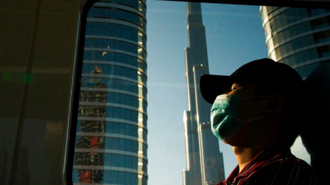 A commuter wearing a face mask to help curb the spread of the coronavirus, sleeps aboard the driverless Metro as it passes the Burj Khalifa in Dubai, United Arab Emirates, Sunday, April 26, 2020. (AP)