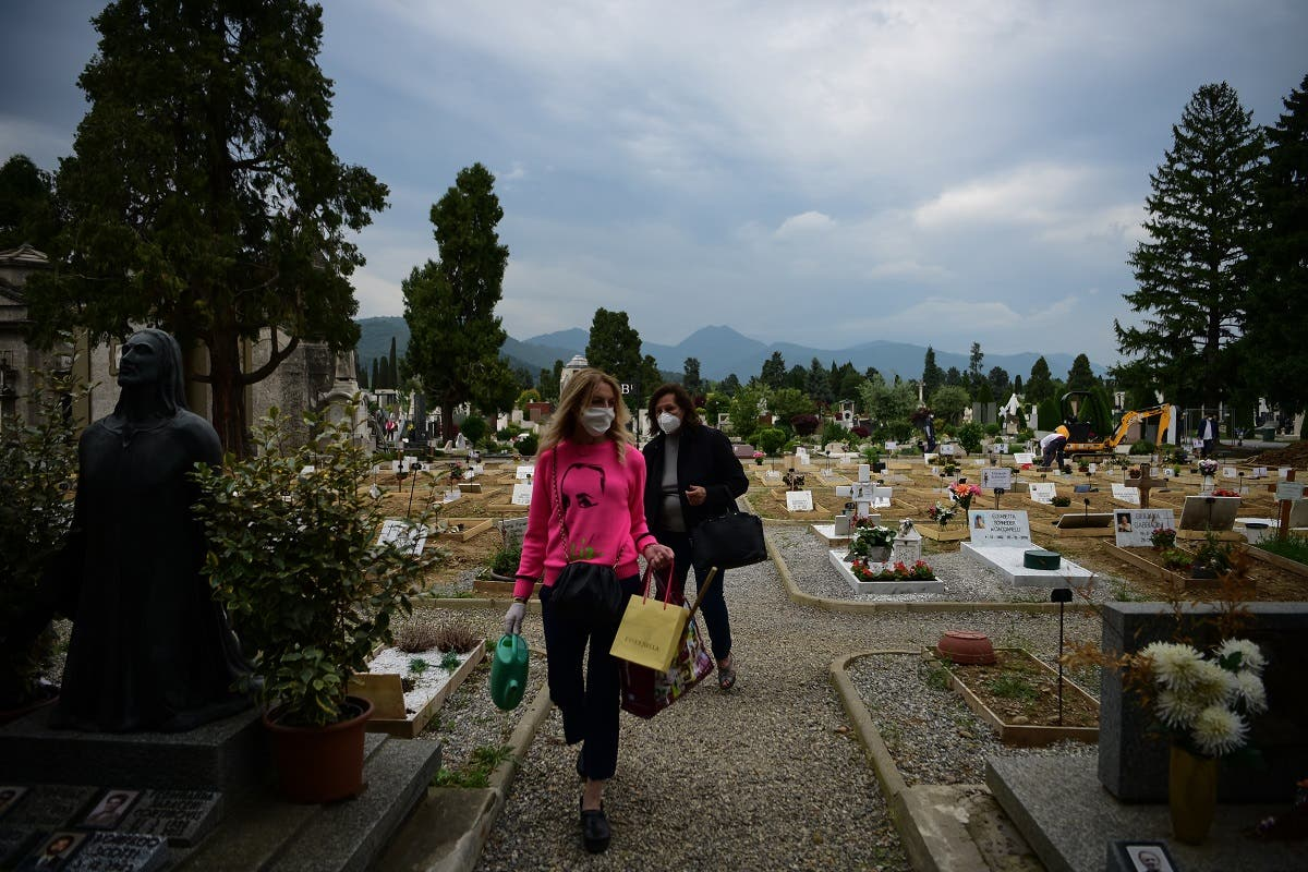 People walk across the Monumental Cemetery of Bergamo, Lombardy, a day after it reopened on May 19, 2020 as the country's is easing its lockdown. (AFP)
