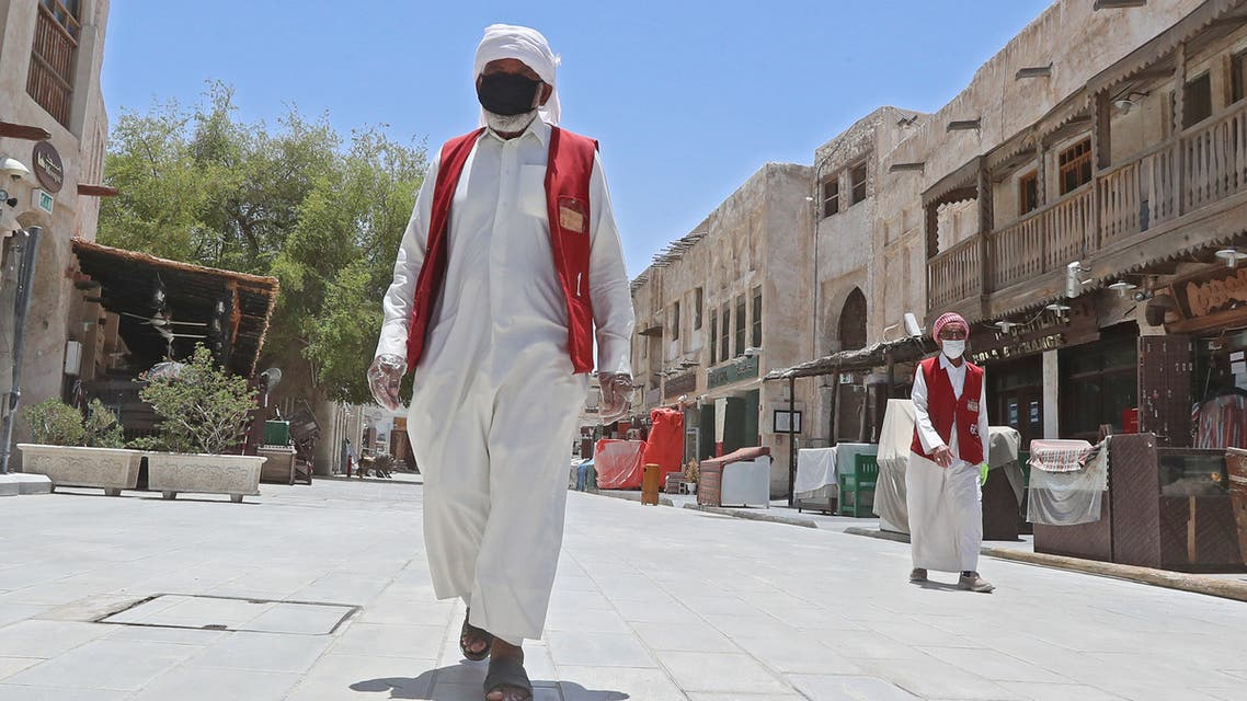 Members of staff wearing masks walk by at Qatar's touristic Souq Waqif bazar in the capital Doha, on May 17, 2020. (AFP)