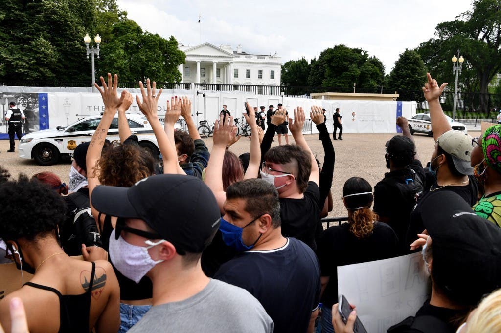 Protesters hold up their hands during a demonstration outside the White House in Washington, DC, on May 29, 2020 over the death of George Floyd. (AFP)