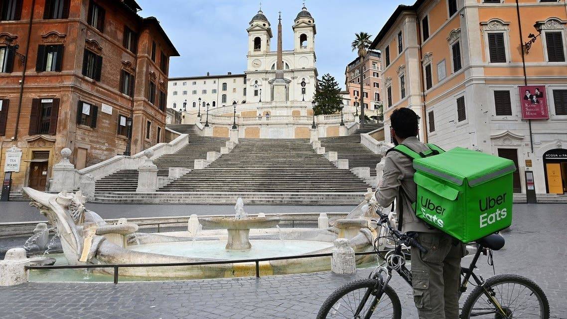 An Uber Eats delivery man stands by the Spanish Steps at a deserted Piazza di Spagna in central Rome on March 12, 2020. (AFP)