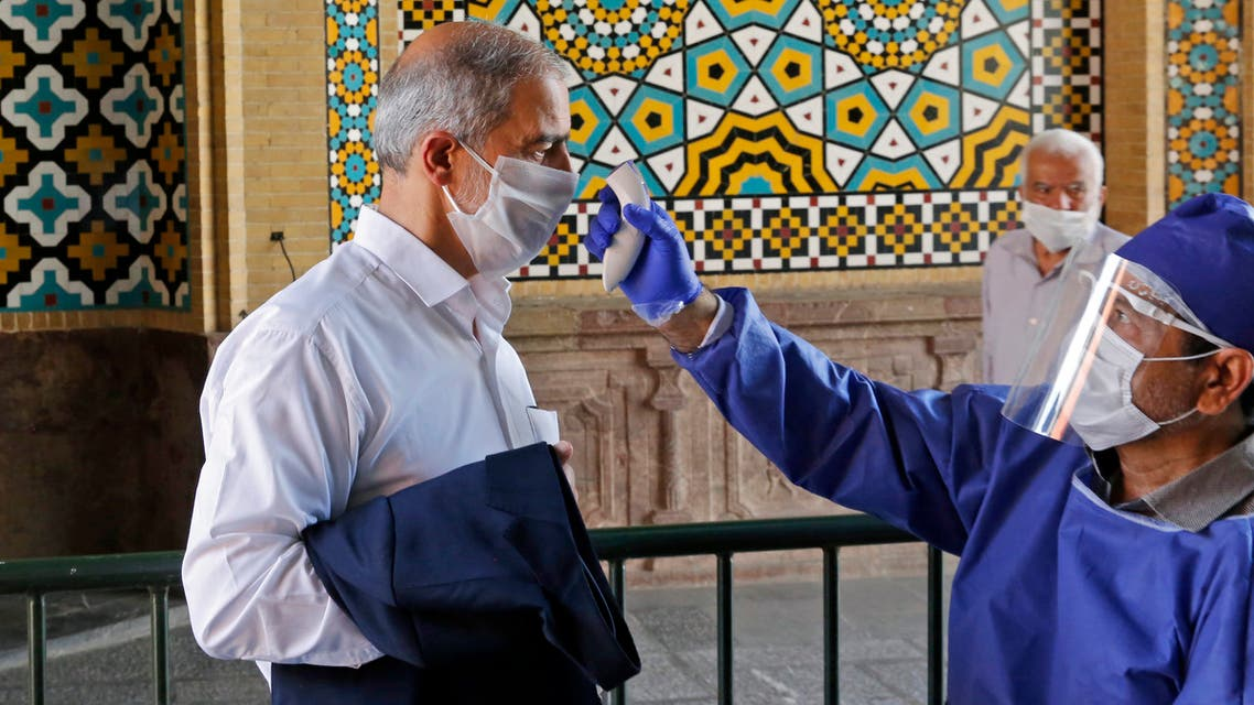 An Iranian official checks the temperature of visitors at the Shah Abdol-Azim shrine in the capital Tehran on May 25, 2020, following the reopening of major Shiite shrines across the Islamic republic, more than two months after they were closed because of the Middle East's deadliest novel coronavirus outbreak.