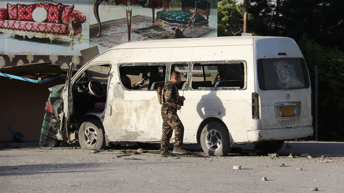 An Afghan security personnel investigates a damaged vehicle carrying employees of Khurshid TV along a roadside, at the site of a bomb blast in Kabul on May 30,2020.
