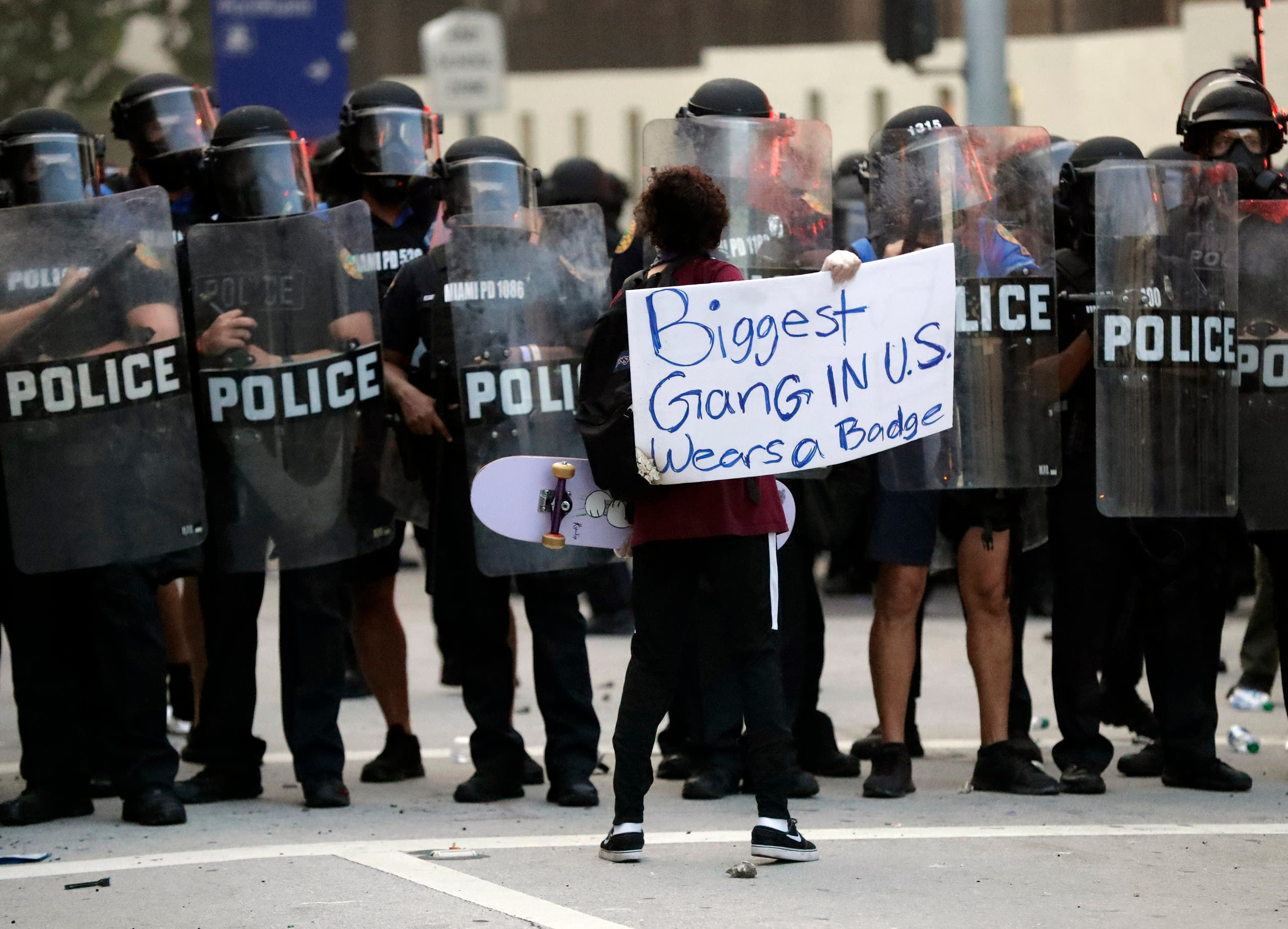 A lone protester confronts a line of police during a demonstration next to the city of Miami Police Department, Saturday, May 30, 2020, downtown in Miami. (AP)