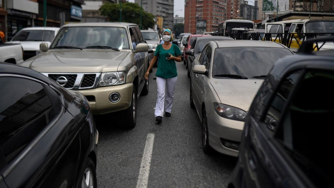 A health worker walks between cars queueing to refuel, near a gas station, in Caracas on May 25, 2020 amid the novel COVID-19 coronavirus outbreak. (AFP)