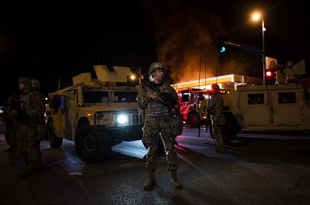 Members of the National Guard hold a perimeter as a fire crew works to put out a fire at a gas station on Lake Street on May 29, 2020 in Minneapolis, Minnesota. (AFP)