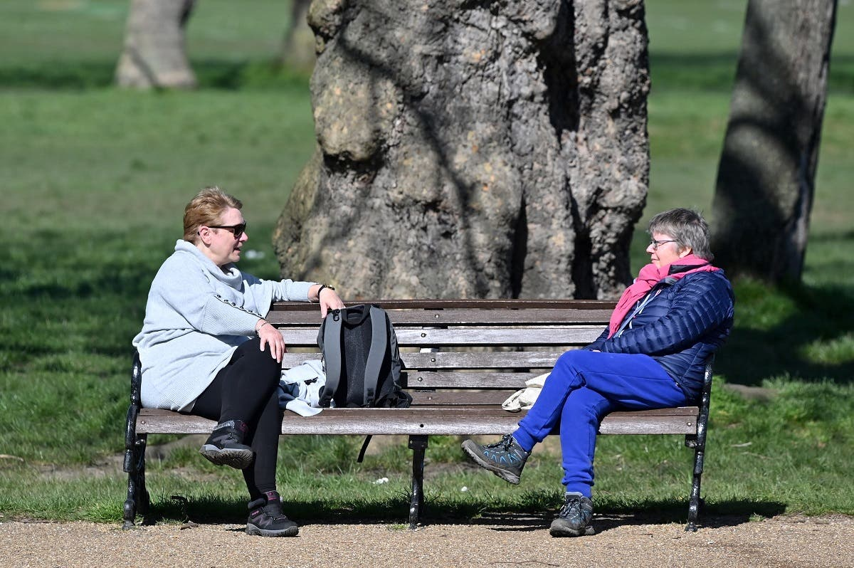 people sit at either end of a park bench as they talk in Clapham Common in south London on March 24, 2020. (AFP)