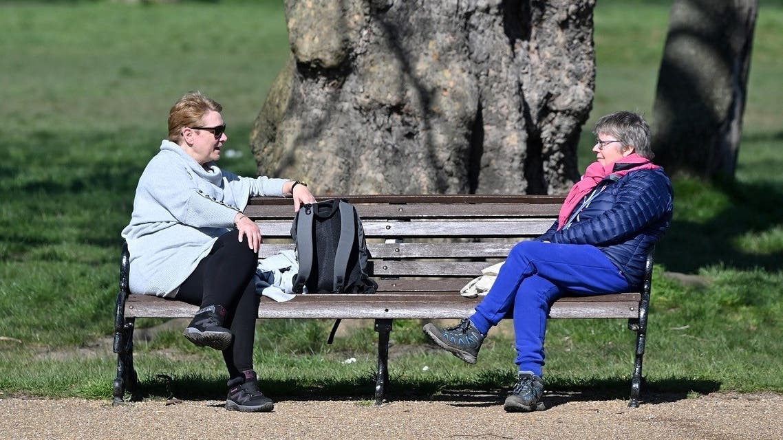 people sit at either end of a park bench as they talk in Clapham Common in south London on March 24, 2020 after Britain's government ordered a lockdown to slow the spread of the novel coronavirus. (AFP)