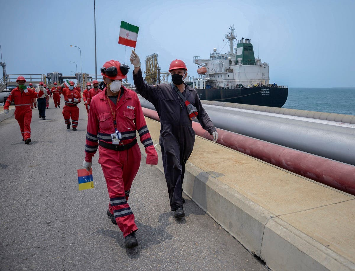 A worker of the Venezuelan state oil company PDVSA waves an Iranian flag as the Iranian-flagged oil tanker Fortune docks at the El Palito refinery in Puerto Cabello, in the northern state of Carabobo, Venezuela, on May 25, 2020. (AFP)