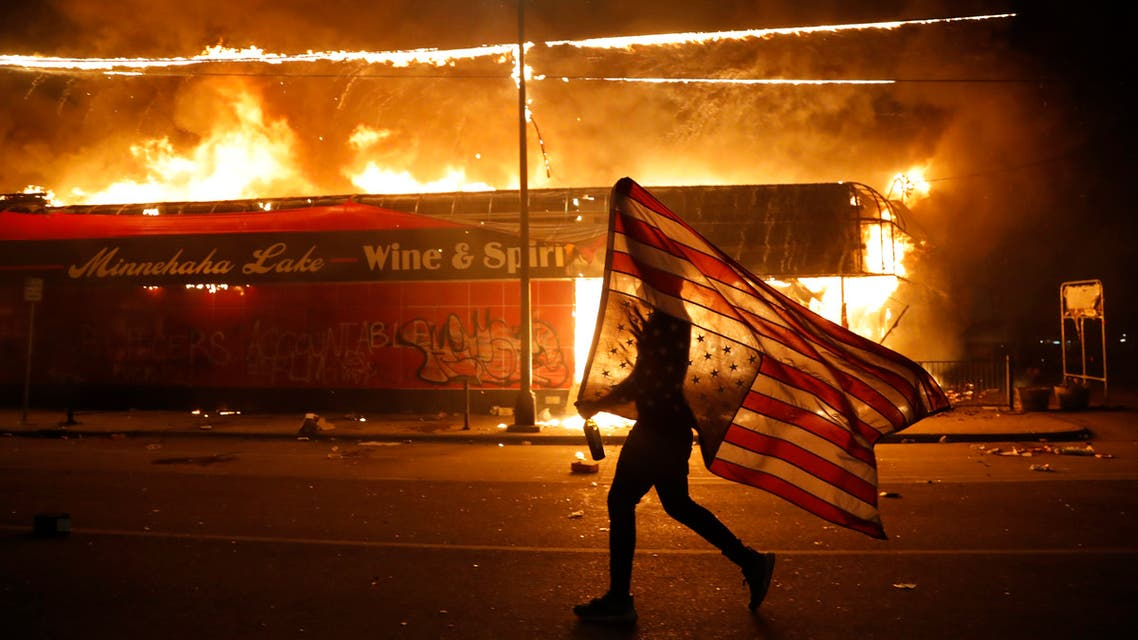 A protester carries a U.S. flag upside down, a sign of distress, next to a burning building Thursday, May 28, 2020, in Minneapolis. (AP)