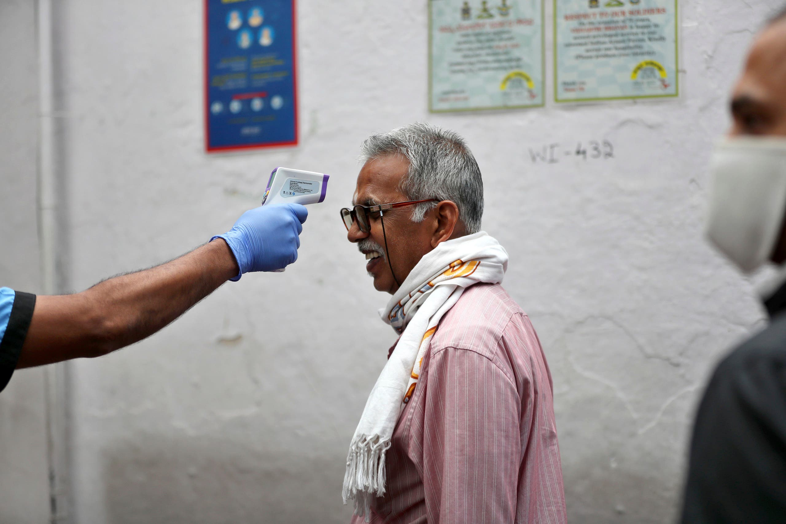 An elderly Indian reacts as a staff member checks his body temperature before allowing him into an eatery in Bengaluru, India on May 30, 2020. (AP)