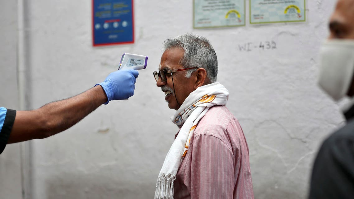 An elderly Indian reacts as a staff member checks his body temperature before allowing him into an eatery in Bengaluru, India, Saturday, May 30, 2020. (AP)