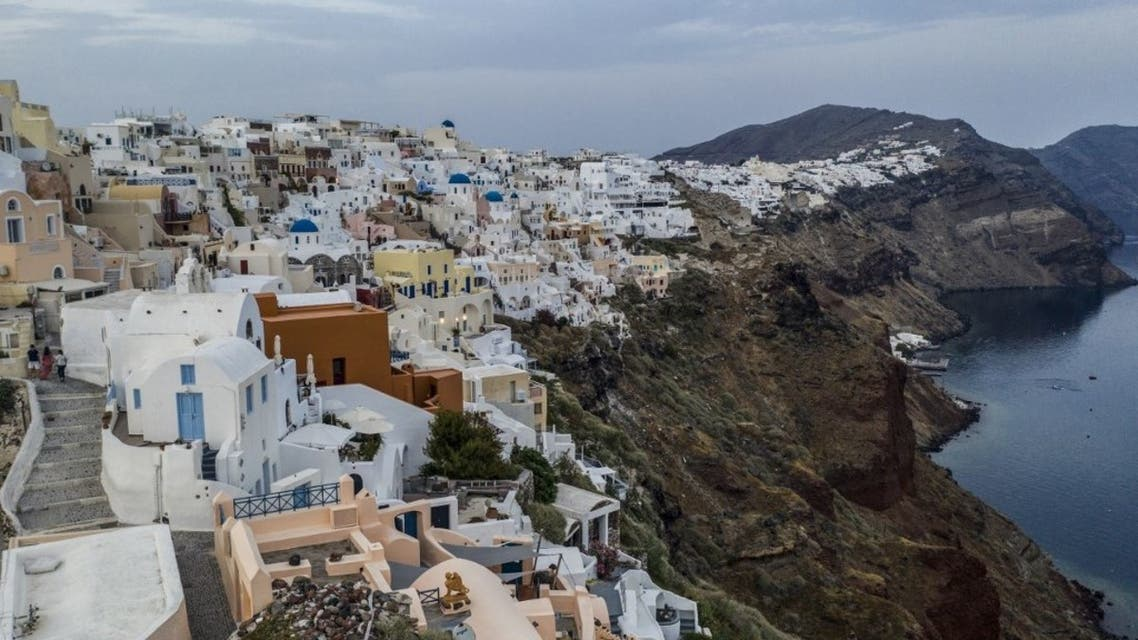 White washed villas adorn the cliffs of the village of Oia, on the northwestern tip of the Greek island of Santorini, in the Aegean Sea on May 20, 2020.  (AFP)