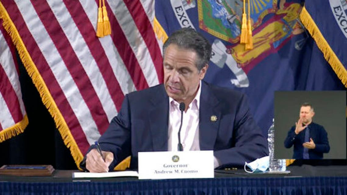 In this image made from video provided by the office of Gov. Andrew M. Cuomo, Gov. Cuomo signs a bill giving death benefits to the families of certain government workers who were killed by coronavirus, Saturday, May 30, 2020 in New York. (AP)