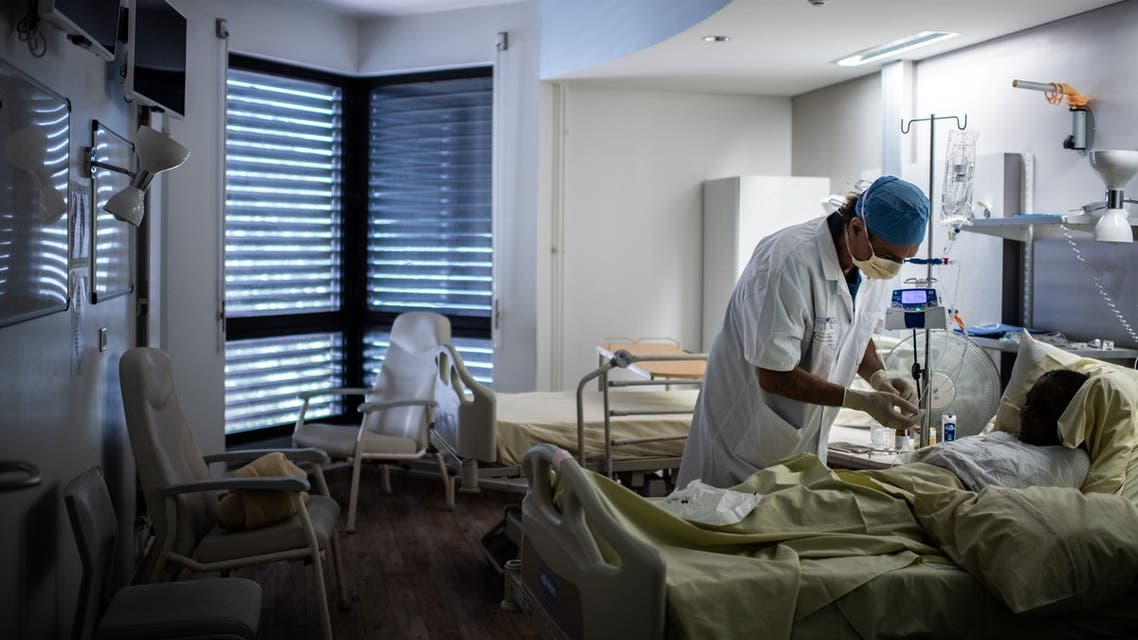 French surgeon Maurice Mimoun chats with a patient at the plastic surgery unit of Saint-Louis hospital of the AP-HP (Assistance Publique - Hopitaux de Paris) in Paris on May 28, 2020 as France eases lockdown measures taken to curb the spread of the COVID-19 (the novel coronavirus).