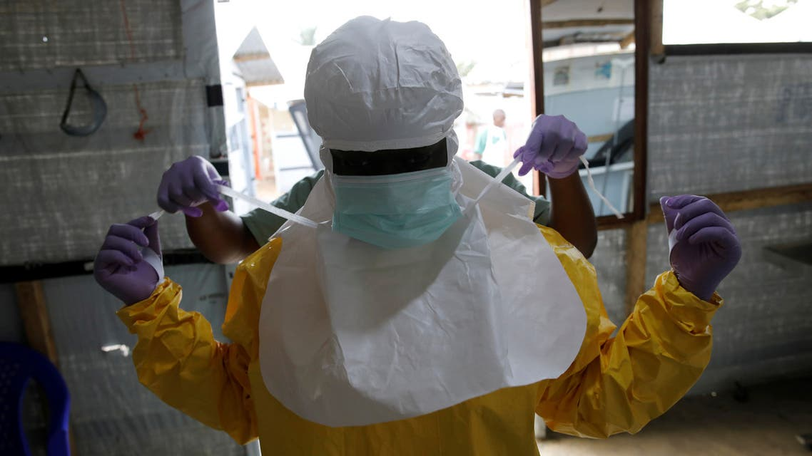 FILE PHOTO: A health worker puts on Ebola protection gear before entering the Biosecure Emergency Care Unit (CUBE) at the ALIMA (The Alliance for International Medical Action) Ebola treatment centre in Beni, in the Democratic Republic of Congo, March 31, 2019. Picture taken March 31, 2019.REUTERS/Baz Ratner/File Photo