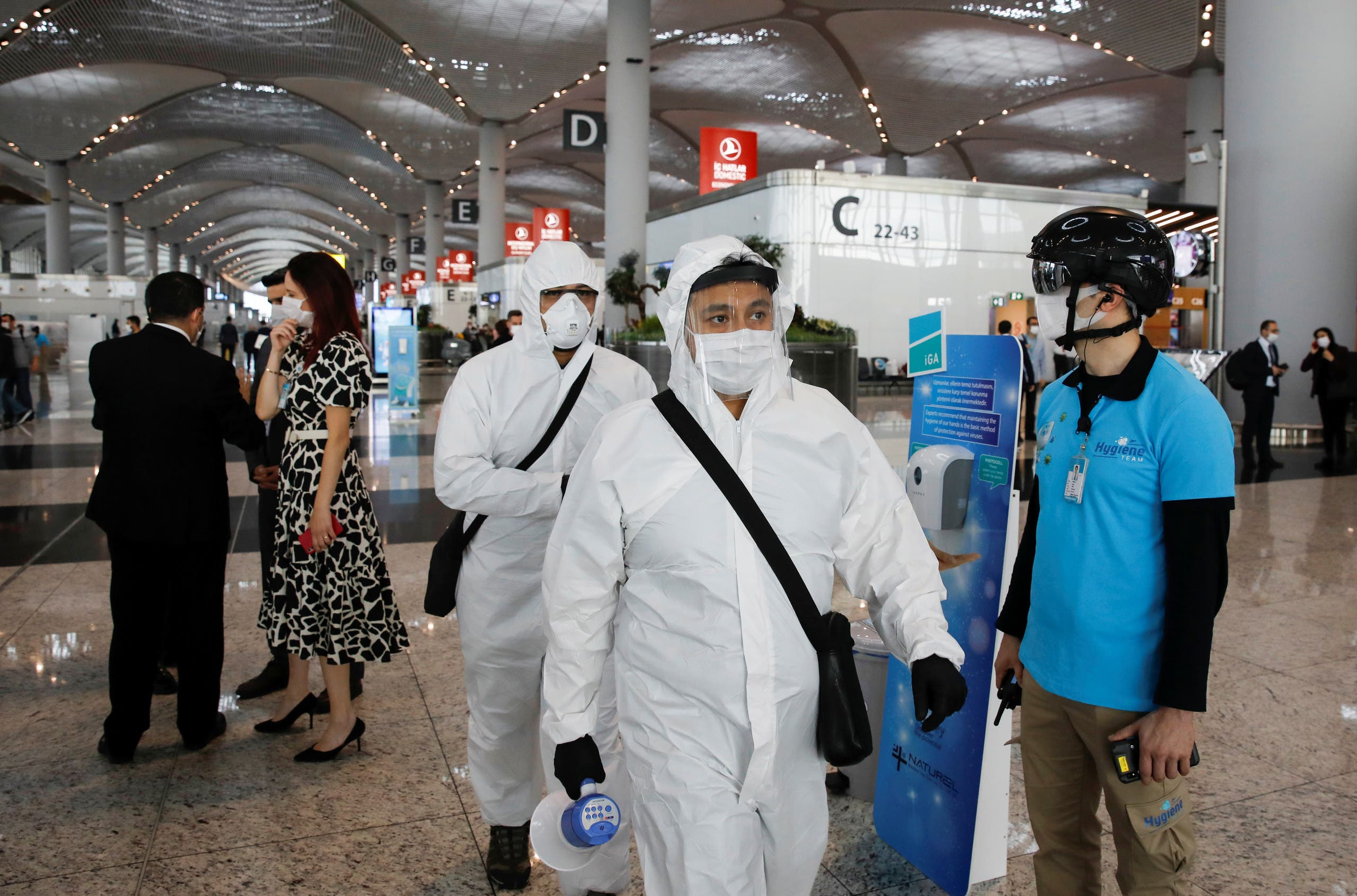 An employee wearing a thermal imaging VF helmet monitors passengers at the entrance of Istanbul Airport, in Istanbul, Turkey June 1, 2020. (Reuters)