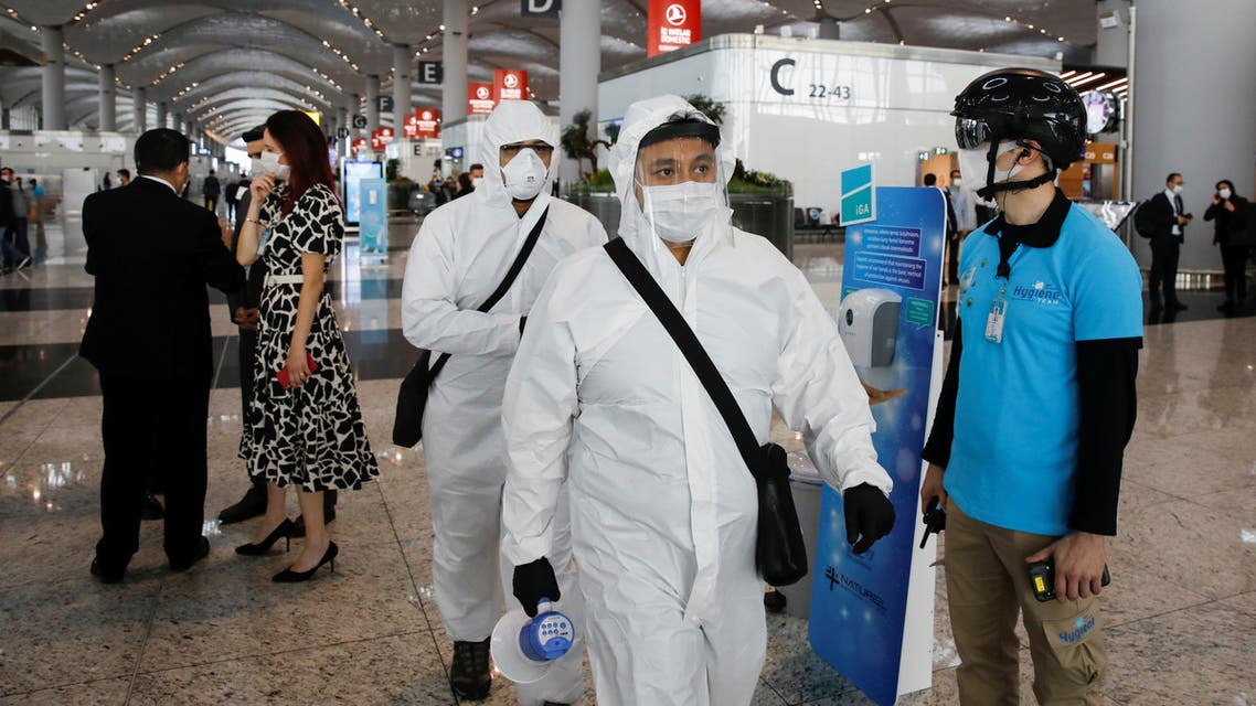 An employee wearing a thermal imaging VF helmet monitors passengers at the entrance of Istanbul Airport during the first day of resumed domestic flights which are halted since March 26 amid the spread of the coronavirus disease (COVID-19), in Istanbul, Turkey June 1, 2020. REUTERS/Umit Bektas