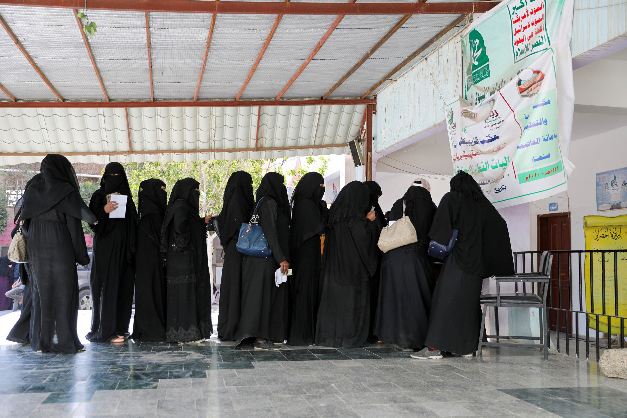 Women stand in line to get food vouchers at a World Food Programme food aid distribution center in Sanaa, Yemen February 11, 2020. (Reuters)