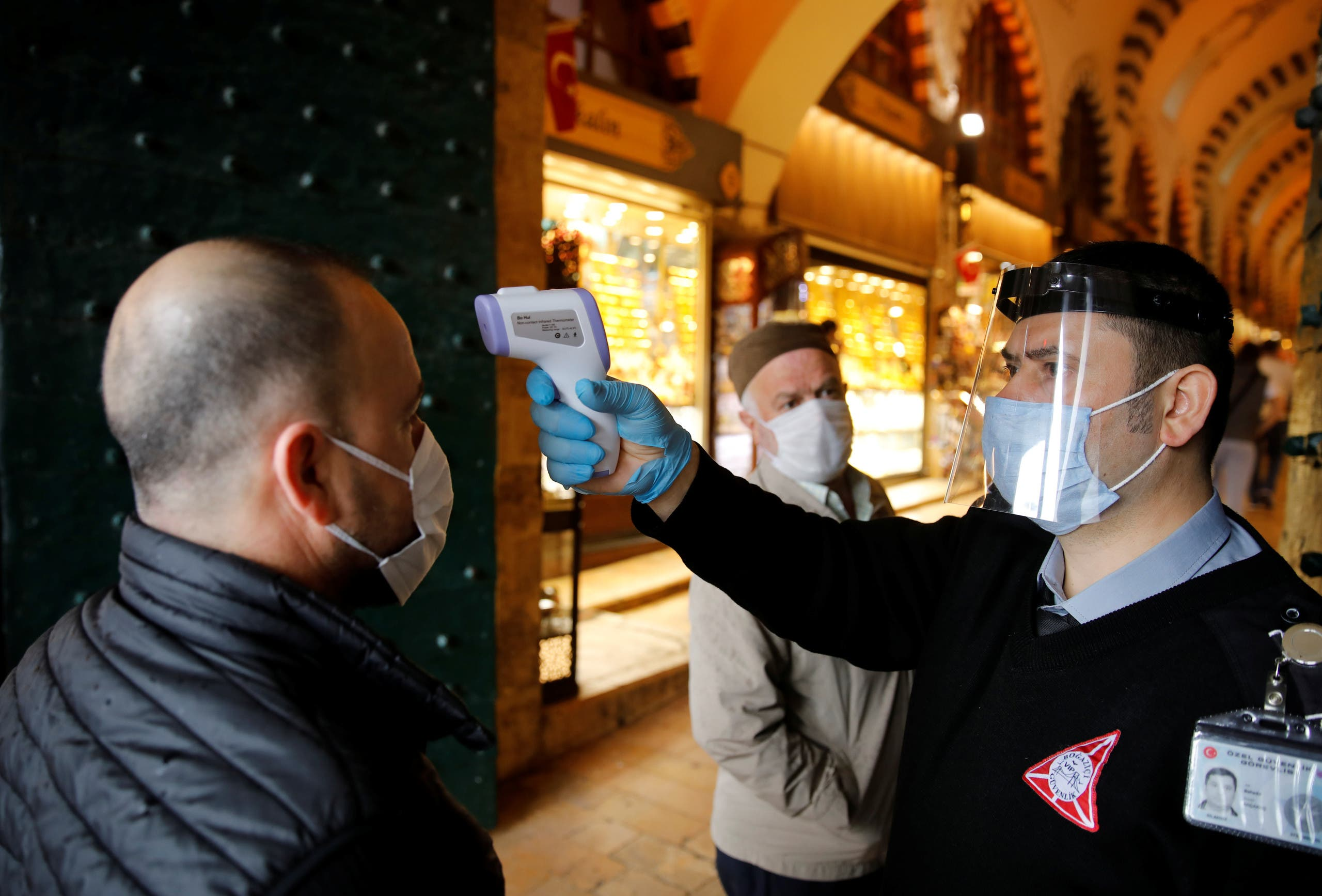 A security guard checks the body temperature of a customer at the entrance of the spice market in Istanbul, Turkey, June 1, 2020. (Reuters)