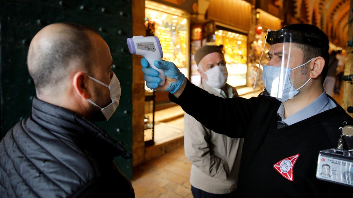A security guard wearing a protective face mask and a visor checks the body temperature of a customer at the entrance of the spice market, also known as the Egyptian Bazaar, as it reopens after weeks of the close doors amid the spread of the coronavirus disease (COVID-19), in Istanbul, Turkey, June 1, 2020. REUTERS/Umit Bektas