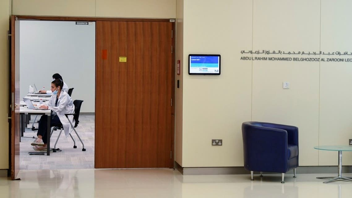 A man wearing a protective mask sits outside a hall where operators man their posts at Dubai's COVID-19 Command and Control Centre at Mohammed bin Rashid University. (AFP)