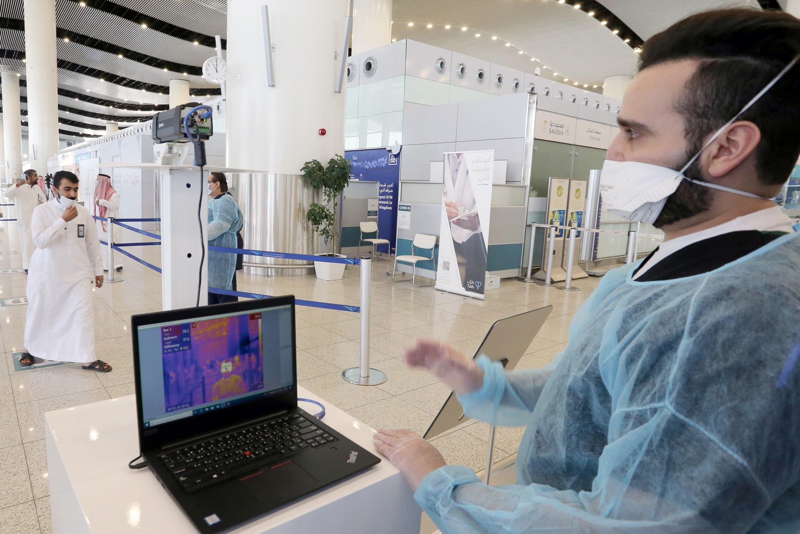 رجل أمن في مطار الرياض الدولي يراقب درجة حرارة المسافرين