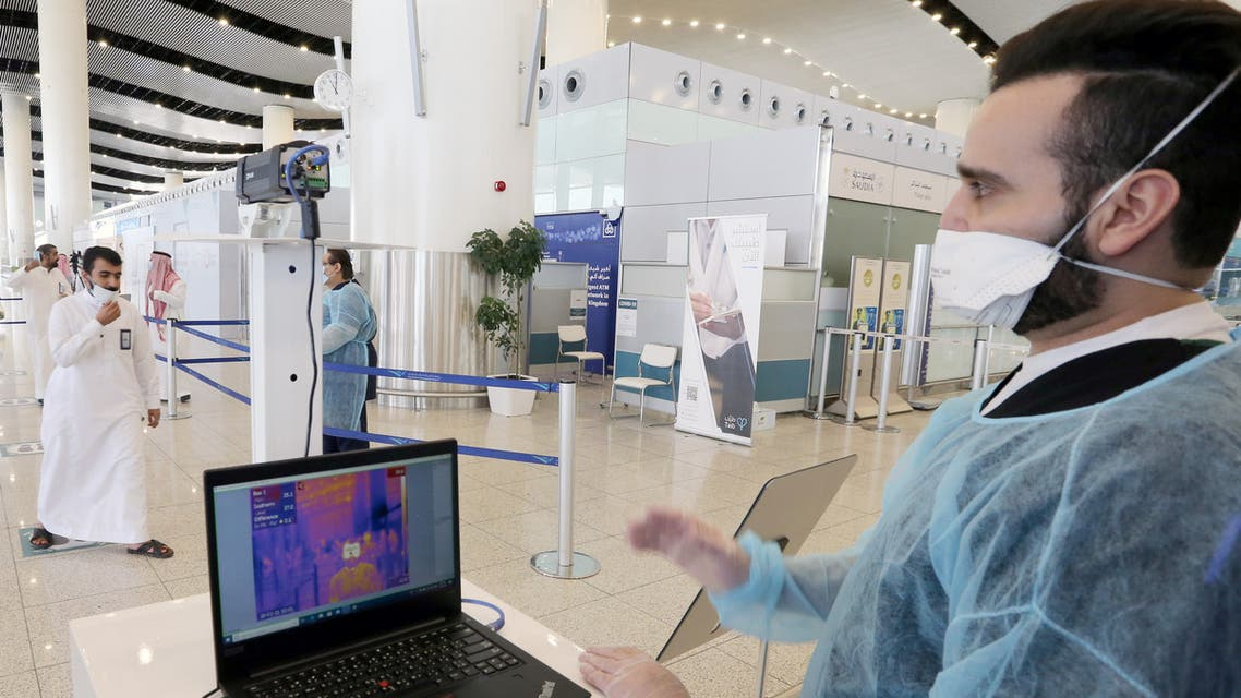 A security man looks at a screen showing the body temperature of travellers, at Riyadh International Airport, after Saudi Arabia reopened domestic flights, following the outbreak of the coronavirus disease (COVID-19), in Riyadh, Saudi Arabia May 31, 2020. REUTERS/Ahmed Yosri