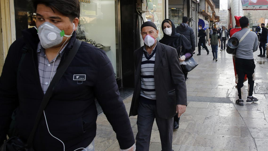 People wearing protective face masks walking along the side of a street by the Tajrish Bazaar in Iran's capital Tehran on March 12, 2020. (AFP)